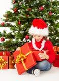 Weihnachtskind in Sankt-Hut, Kinderoffenes Geschenkboxgeschenk, Weihnachtsbaum Lizenzfreie Stockbilder