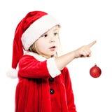 Weihnachtskind in Santa Hat mit neues Jahr ` s Glaskugel lokalisiert Lizenzfreie Stockbilder