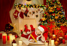 Weihnachtskind schreiben Wunschliste, Kind Santa Hat Writing Letter Stockfotos