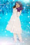 Weihnachtskindermädchen auf Winterbaumhintergrund, Schnee, Schneeflocken Stockfoto