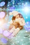 Weihnachtskindermädchen auf Winterbaumhintergrund, Schnee, Schneeflocken Stockfotografie