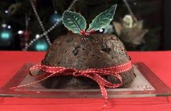 Weihnachtsklassischer Pflaumenpudding mit Stechpalme auf roter Tischdecke Lizenzfreie Stockfotos