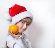 Weihnachtskleines Mädchen und -orange stockfotos