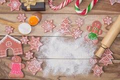 Weihnachtskochen Mehl für das Backen, die Eier, die Ingwerkekse und Lebkuchenmann auf hölzernem Hintergrund mit freiem Raum für T lizenzfreies stockfoto