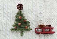 Weihnachtskonzept mit Fichte, Tannenbaum, Kegel und Pferdeschlitten auf Weiß strickte Hintergrund Abbildung der roten Lilie Lizenzfreie Stockfotografie
