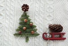 Weihnachtskonzept mit Fichte, Tannenbaum, Kegel und Pferdeschlitten auf Weiß strickte Hintergrund Mit zusätzlichem vektorformat Lizenzfreie Stockfotos