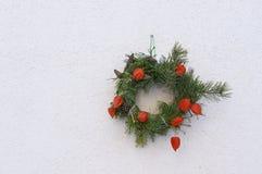 Weihnachtskranz auf der Wand des Hauses Stockbilder