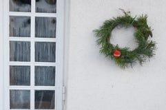 Weihnachtskranz auf der Wand des Hauses Lizenzfreies Stockfoto
