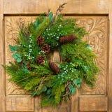 WeihnachtsKranz auf Holztür Stockfotografie