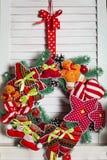 Weihnachtskranz, der an den hölzernen Vorhängen hängt Lizenzfreies Stockfoto