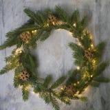 Weihnachtskranz gemacht von den Tannenzweigen, von den Plätzchen und von glühenden Lichtern auf grauem Hintergrund Hintergrund de lizenzfreie stockfotografie