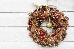 Weihnachtskranz gemacht von der Kiefer und von den Tannenzapfen auf der Wand des Hauses stockfotos