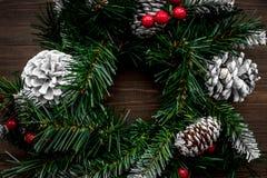 Weihnachtskranz gesponnen von den Fichtenzweigen mit roten Beeren auf Draufsicht des hölzernen Hintergrundes Stockbild
