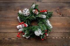 Weihnachtskranz gesponnen von den Fichtenzweigen mit roten Beeren auf Draufsicht des hölzernen Hintergrundes Lizenzfreies Stockbild