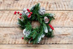 Weihnachtskranz gesponnen von den Fichtenzweigen mit roten Beeren auf Draufsicht des hellen hölzernen Hintergrundes Lizenzfreie Stockfotos