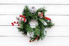 Weihnachtskranz gesponnen von den Fichtenzweigen mit roten Beeren auf Draufsicht des weißen hölzernen Hintergrundes Lizenzfreies Stockfoto