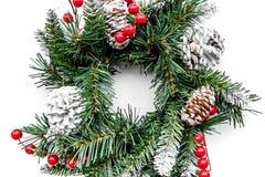 Weihnachtskranz gesponnen von den Fichtenzweigen mit roten Beeren auf Draufsicht des weißen Hintergrundes Stockbilder