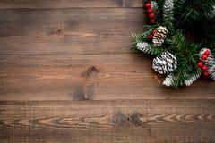 Weihnachtskranz gesponnen von den Fichtenzweigen mit roten Beeren auf hölzernem copyspace Draufsicht des Hintergrundes Stockfoto