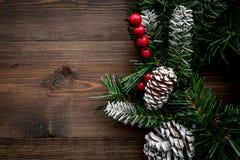 Weihnachtskranz gesponnen von den Fichtenzweigen mit roten Beeren auf hölzernem copyspace Draufsicht des Hintergrundes Stockbild