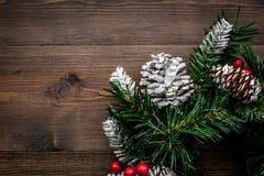Weihnachtskranz gesponnen von den Fichtenzweigen mit roten Beeren auf hölzernem copyspace Draufsicht des Hintergrundes Stockfotos
