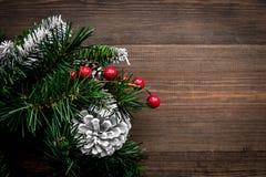 Weihnachtskranz gesponnen von den Fichtenzweigen mit roten Beeren auf hölzernem copyspace Draufsicht des Hintergrundes Stockfotografie