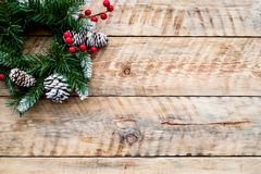 Weihnachtskranz gesponnen von den Fichtenzweigen mit roten Beeren auf hellem hölzernem copyspace Draufsicht des Hintergrundes Stockfoto