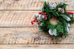 Weihnachtskranz gesponnen von den Fichtenzweigen mit roten Beeren auf hellem hölzernem copyspace Draufsicht des Hintergrundes Lizenzfreies Stockbild
