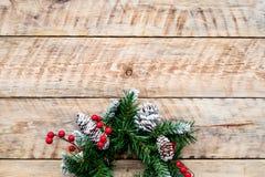 Weihnachtskranz gesponnen von den Fichtenzweigen mit roten Beeren auf hellem hölzernem copyspace Draufsicht des Hintergrundes Stockfotografie