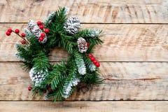 Weihnachtskranz gesponnen von den Fichtenzweigen mit roten Beeren auf hellem hölzernem copyspace Draufsicht des Hintergrundes Stockfotos