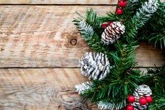 Weihnachtskranz gesponnen von den Fichtenzweigen mit roten Beeren auf hellem hölzernem Draufsicht-Nahaufnahme copyspace des Hinte Stockbild