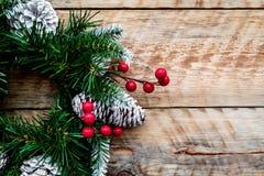 Weihnachtskranz gesponnen von den Fichtenzweigen mit roten Beeren auf hellem hölzernem Draufsicht-Nahaufnahme copyspace des Hinte Stockbilder