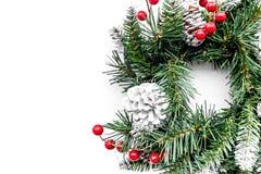 Weihnachtskranz gesponnen von den Fichtenzweigen mit roten Beeren auf weißem copyspace Draufsicht des Hintergrundes Lizenzfreie Stockfotos