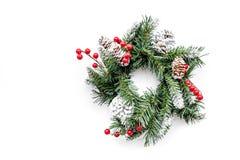Weihnachtskranz gesponnen von den Fichtenzweigen mit roten Beeren auf weißem copyspace Draufsicht des Hintergrundes Stockfotografie