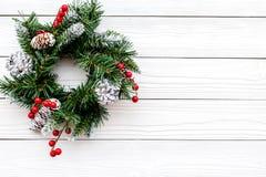 Weihnachtskranz gesponnen von den Fichtenzweigen mit roten Beeren auf weißem hölzernem copyspace Draufsicht des Hintergrundes Lizenzfreies Stockbild