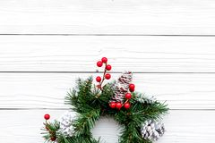 Weihnachtskranz gesponnen von den Fichtenzweigen mit roten Beeren auf weißem hölzernem copyspace Draufsicht des Hintergrundes Stockfotos
