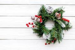 Weihnachtskranz gesponnen von den Fichtenzweigen mit roten Beeren auf weißem hölzernem copyspace Draufsicht des Hintergrundes Stockbilder