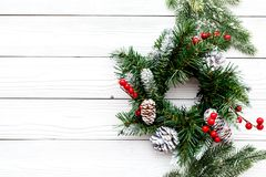 Weihnachtskranz gesponnen von den Fichtenzweigen mit roten Beeren auf weißem hölzernem copyspace Draufsicht des Hintergrundes Stockbild