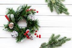 Weihnachtskranz gesponnen von den Fichtenzweigen mit roten Beeren auf weißem hölzernem copyspace Draufsicht des Hintergrundes Stockfoto