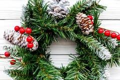 Weihnachtskranz gesponnen von den Fichtenzweigen mit roten Beeren auf weißer hölzerner Draufsichtnahaufnahme des Hintergrundes Lizenzfreie Stockfotografie