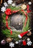 Weihnachtskranz, Schneeflocken, rotes Band und verschiedene Winterdekorationen auf rustikalem hölzernem Hintergrund Stockbild