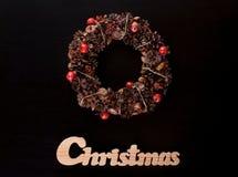 Weihnachtskranz und Weihnachtshölzernes Schreiben auf Schwarzem Stockfoto