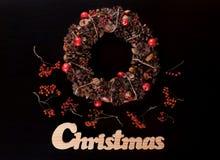 Weihnachtskranz und Weihnachtshölzernes Schreiben auf Schwarzem Stockbilder