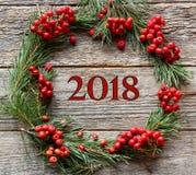 Weihnachtskranz von Kiefernniederlassungen und von roter Eberesche auf hölzernem Hintergrund Aufschrift 2018 des neuen Jahres Lizenzfreies Stockbild