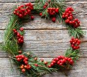 Weihnachtskranz von Kiefernniederlassungen und von roter Eberesche auf hölzernem Hintergrund Kopieren Sie Platz Lizenzfreies Stockfoto