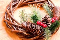 Weihnachtskranz von Zweigen mit Kiefernnadeln und von Kegeln auf einem yello Lizenzfreies Stockbild