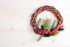 Weihnachtskranz von Zweigen mit Kiefernnadeln und von Kegeln auf Licht b Lizenzfreies Stockfoto