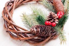 Weihnachtskranz von Zweigen mit Kiefernnadeln und von Kegeln auf Licht b Stockbilder