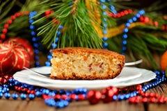 Weihnachtskuchen auf weißer Platte mit Pelzbaum- und -weihnachtsspielwaren Lizenzfreies Stockfoto