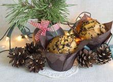 Weihnachtskuchen in der Papierverpackung, in den Weihnachtslichtern und im Kiefernblumenstrauß auf einem Leinenhintergrund Stockfotografie