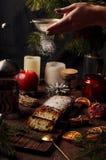 Weihnachtskuchen, in Deutschland christstollen, Frauenhandbesprühen Stockfotos